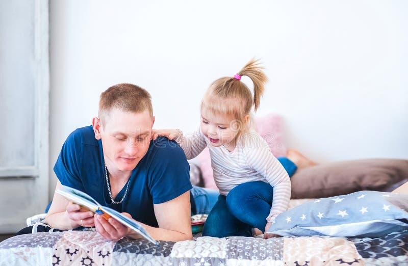 De papa in een blauwe T-shirt leest boeken, sprookjes van een kleine dochter met een grappige staart in een roze sweater Familie  stock afbeeldingen