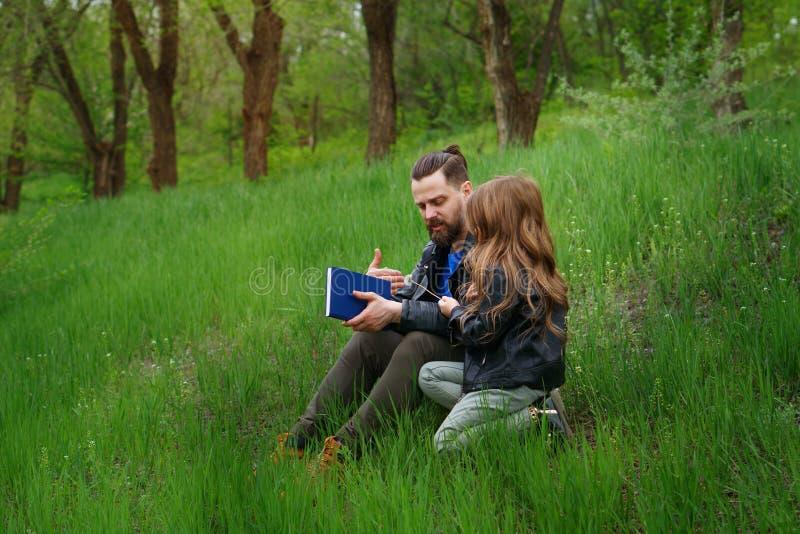 De papa en de dochter brengen samen tijd in park door stock fotografie