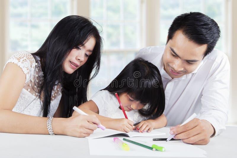 De papa en het mamma helpen hun dochter die thuiswerk doen stock afbeelding