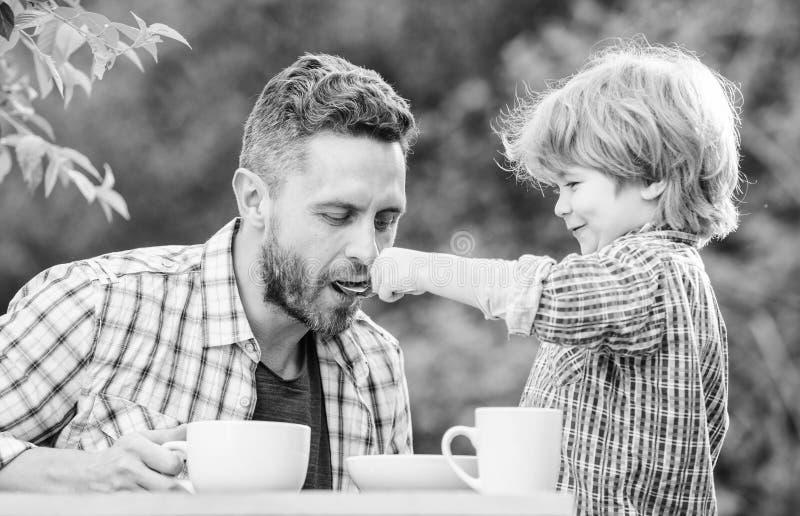 De papa en de jongen eten in openlucht en voeden elkaar Manieren om gezonde eetgewoonten te ontwikkelen Voed uw baby Natuurlijke  stock foto
