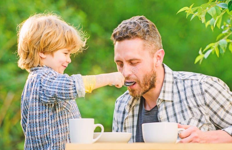 De papa en de jongen eten in openlucht en voeden elkaar Manieren om gezonde eetgewoonten te ontwikkelen Voed uw baby Natuurlijke  royalty-vrije stock fotografie