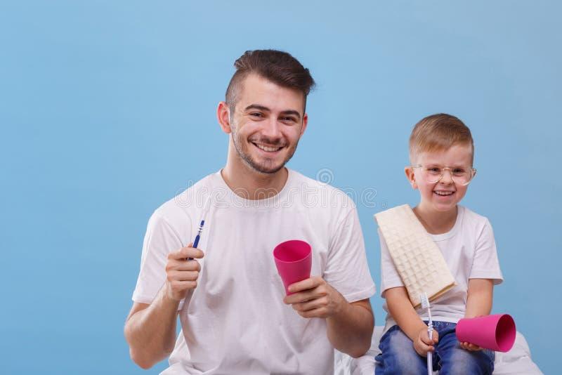 De papa en zijn zoon gaan hun tanden op een blauwe achtergrond borstelen royalty-vrije stock afbeeldingen