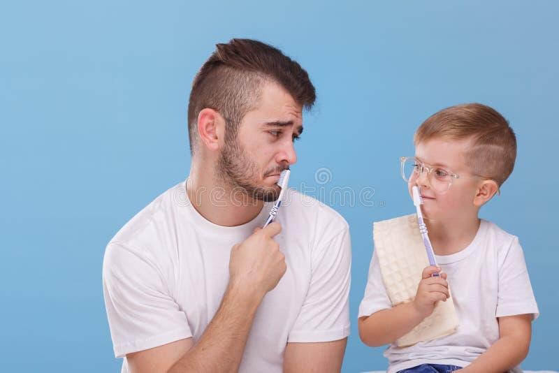 De papa en zijn zoon zetten borstels aan hun lippen en bekijken elkaar tegen een blauwe achtergrond royalty-vrije stock foto