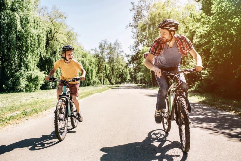 De papa en de zoon berijden op fietsen Zij hebben de concurrentie De kerels bekijken elkaar royalty-vrije stock foto's
