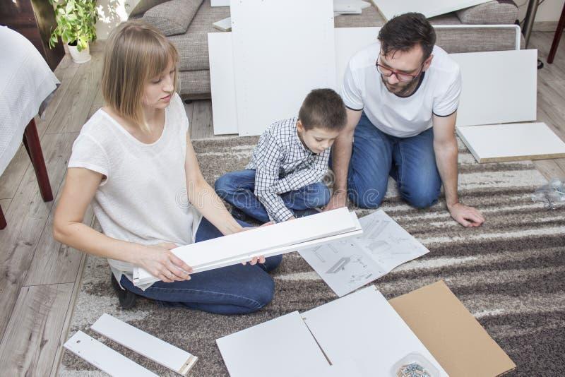 De papa en de zoon besteden samen hun vrije tijd rollend meubilair Het mamma houdt witte lange elementen in haar handen royalty-vrije stock afbeelding