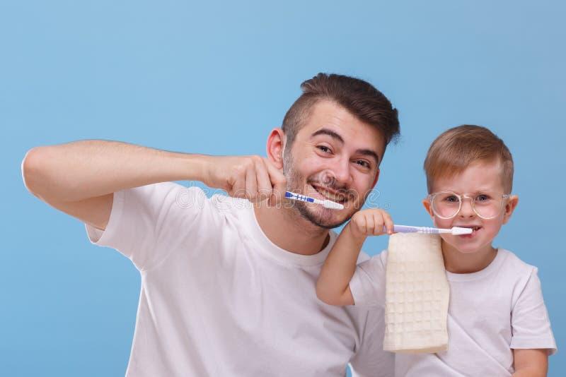 De papa en de zoon borstelen hun tandenclose-up op een blauwe achtergrond royalty-vrije stock afbeelding