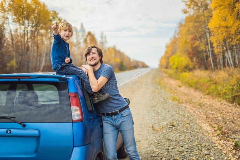De papa en de zoon rusten op de kant van de weg op een wegreis Wegreis met kinderenconcept royalty-vrije stock foto's