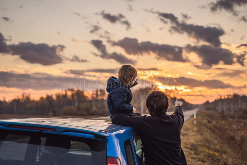De papa en de zoon rusten op de kant van de weg op een wegreis Wegreis met kinderenconcept royalty-vrije stock afbeelding