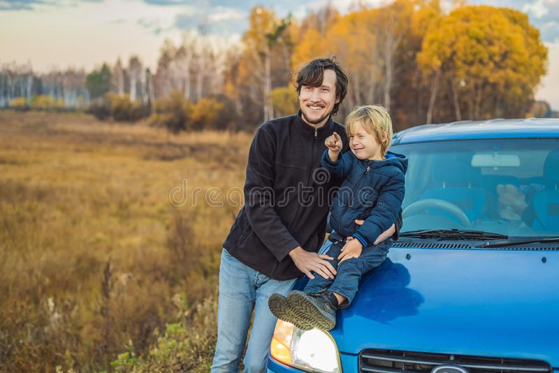 De papa en de zoon rusten op de kant van de weg op een wegreis Wegreis met kinderenconcept stock afbeelding