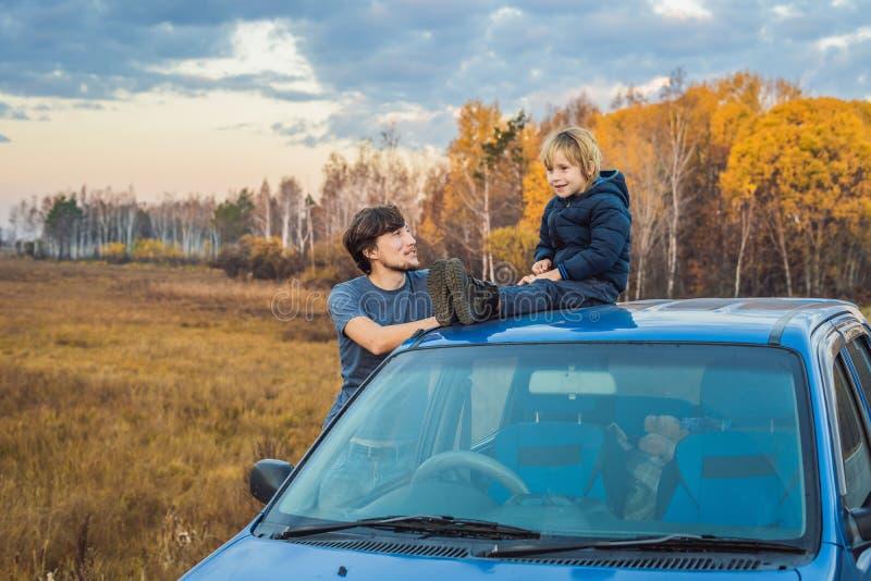 De papa en de zoon rusten op de kant van de weg op een wegreis Wegreis met kinderenconcept stock foto