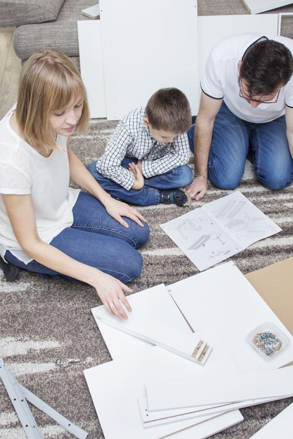 De papa en de zoon staren bij de instructies van de meubilairassemblage knielend op het tapijt Het mamma kiest één element van ve royalty-vrije stock afbeeldingen