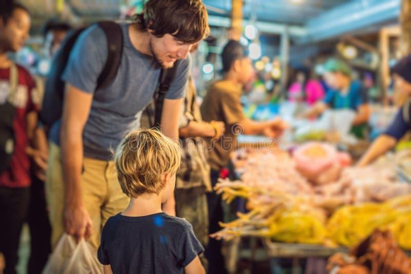 De papa en de zoon zijn toeristen op het Lopen markt van het straat de Aziatische voedsel stock afbeelding