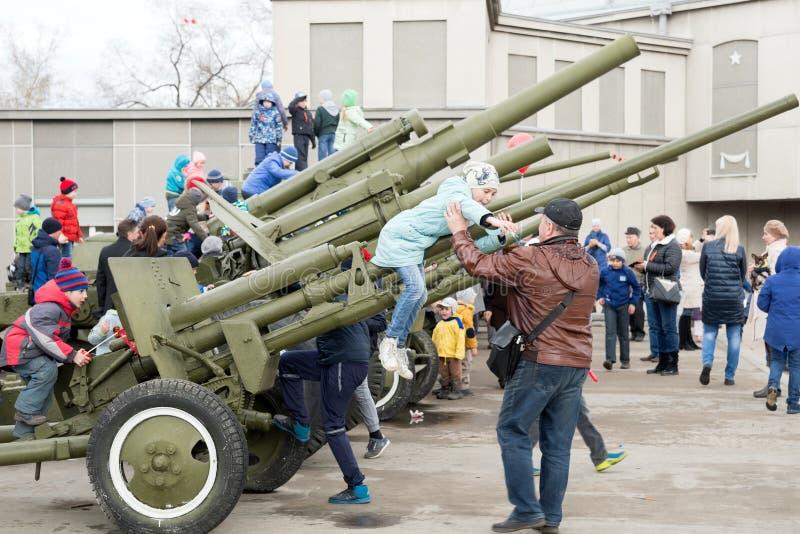 De papa helpt dochter om van het luchtafweerkanon te krijgen, dat zich dichtbij het museum van Victory Memorial bevindt stock afbeeldingen