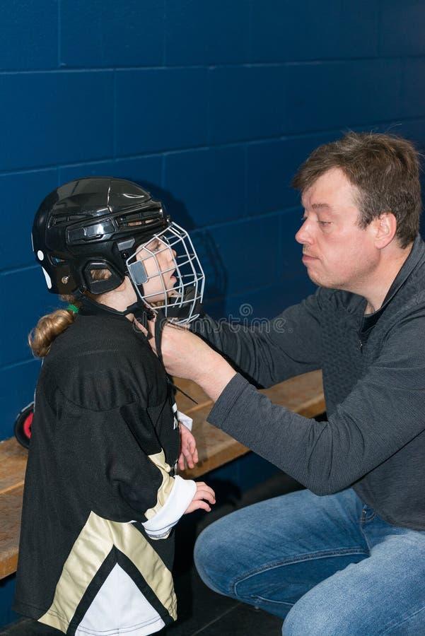 De papa helpt weinig leuk blondemeisje om hockeyhelm te dragen Het meisje draagt in volledig hockeymateriaal royalty-vrije stock afbeelding