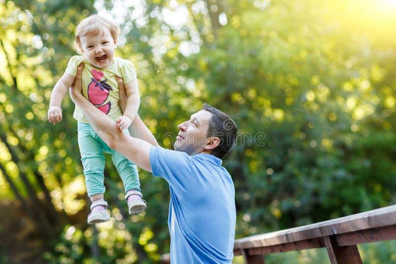 De papa houdt babydochter in zijn wapens in de zomerpark stock foto