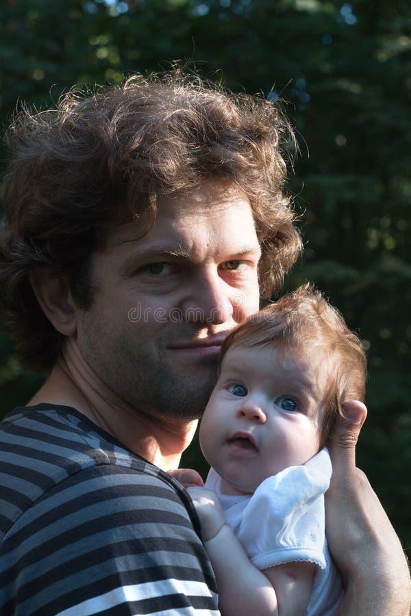 De papa houdt een dochter in zijn wapens voor een gang in het park De lentedag, familiegang in zonnige aard, royalty-vrije stock fotografie