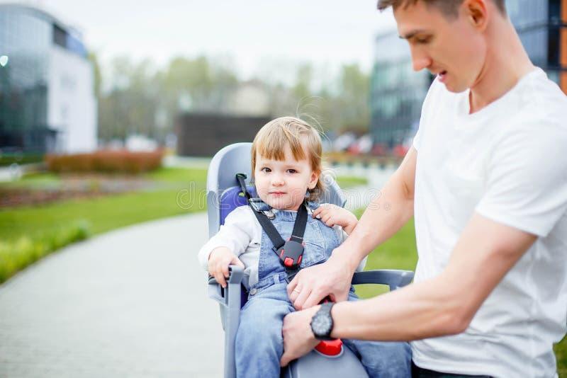 De papa maakt zijn dochter` s veiligheidsgordels vast alvorens een fiets te berijden royalty-vrije stock foto