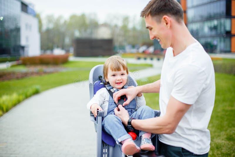 De papa maakt zijn dochter` s veiligheidsgordels vast alvorens een fiets te berijden stock afbeeldingen