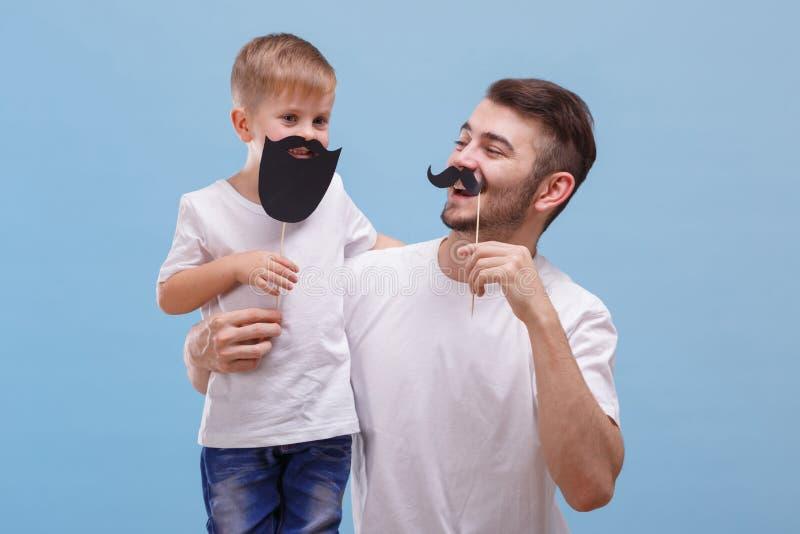 De papa met een glimlach bekijkt zijn zoon naast een blauwe achtergrond stock foto's