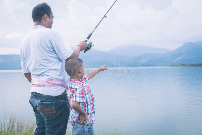 De papa onderwijst zijn zoon visserij stock afbeeldingen