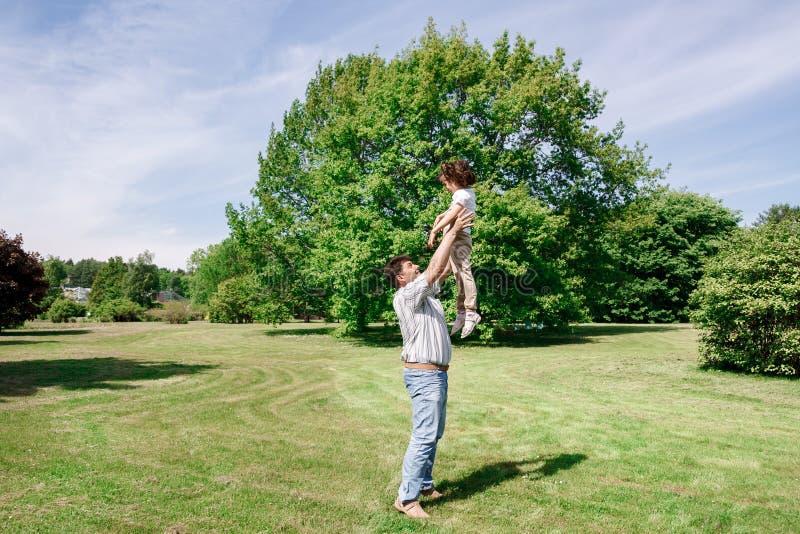 De papaspelen met zijn dochter werpt haar omhooggaand en vangsten stock foto's