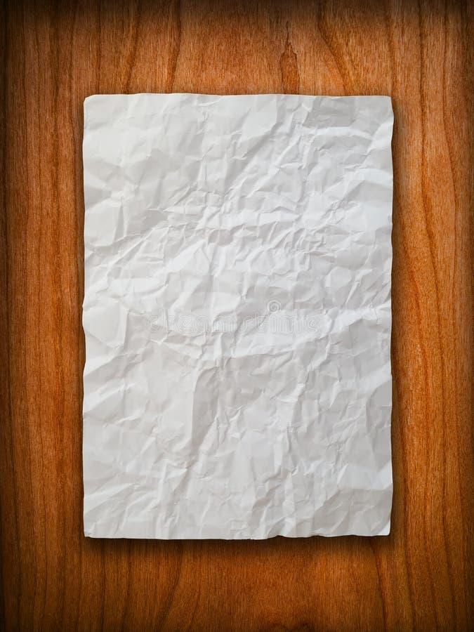 De papel amarrotado na parede de madeira imagem de stock