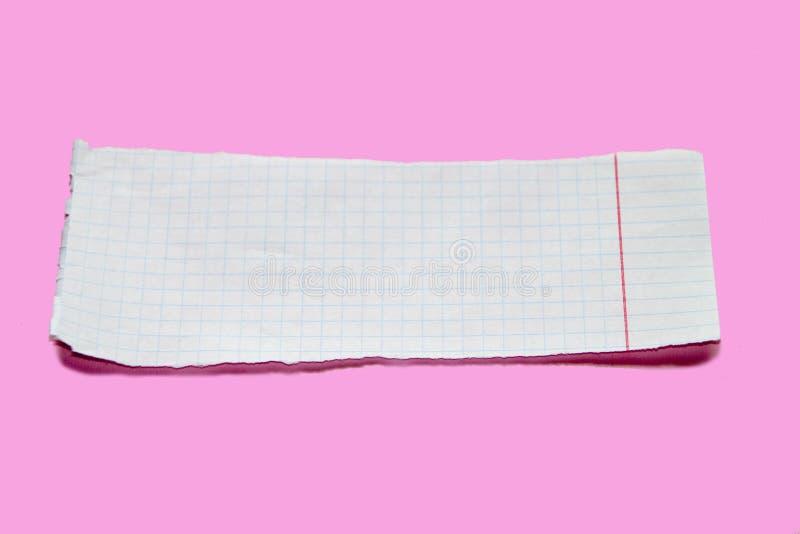 De papel rasgada en fondo rosado Esconda la hoja rasgada del cuaderno foto de archivo libre de regalías