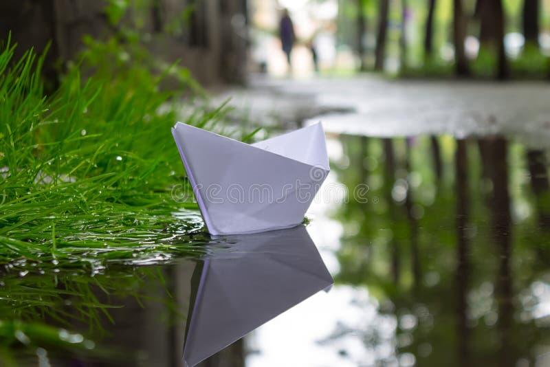 De pappers- fartygflötena på strömmen efter en hällregn mellan gatorna av staden royaltyfri bild