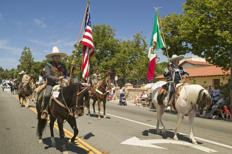 De paradedeelnemers op horseback die Amerikaanse en Mexicaanse vlaggen dragen maken hun manier onderaan hoofdstraat tijdens een V stock fotografie