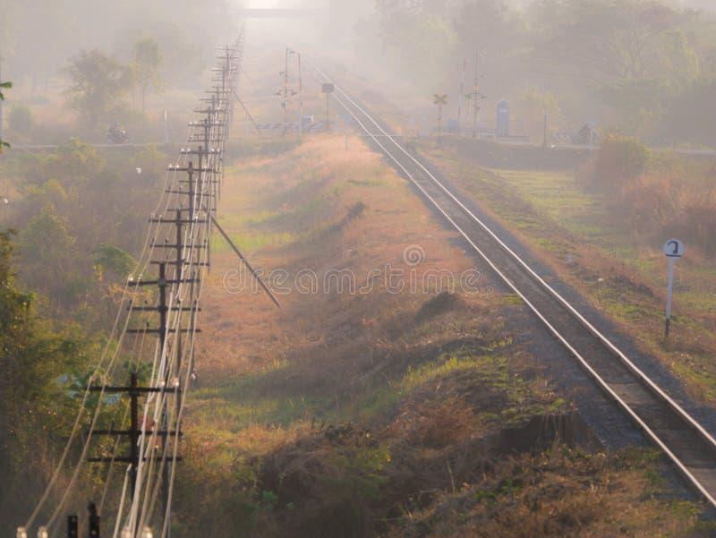 De Parallel van spoorpool aan het Treinspoor op de Mistdag stock fotografie