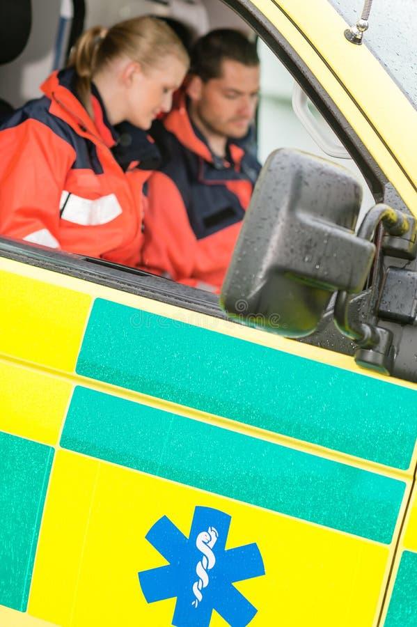 De paramedici die van de de ziekenwagenauto van de noodsituatie het werk zitten royalty-vrije stock afbeeldingen