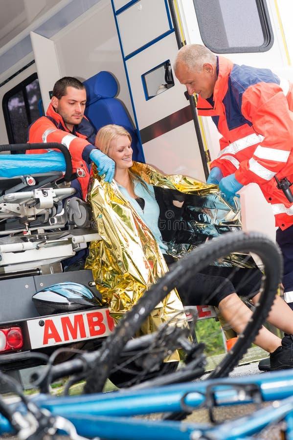 De paramedici die van de noodsituatie het ongeval van de vrouwenfiets helpen stock fotografie