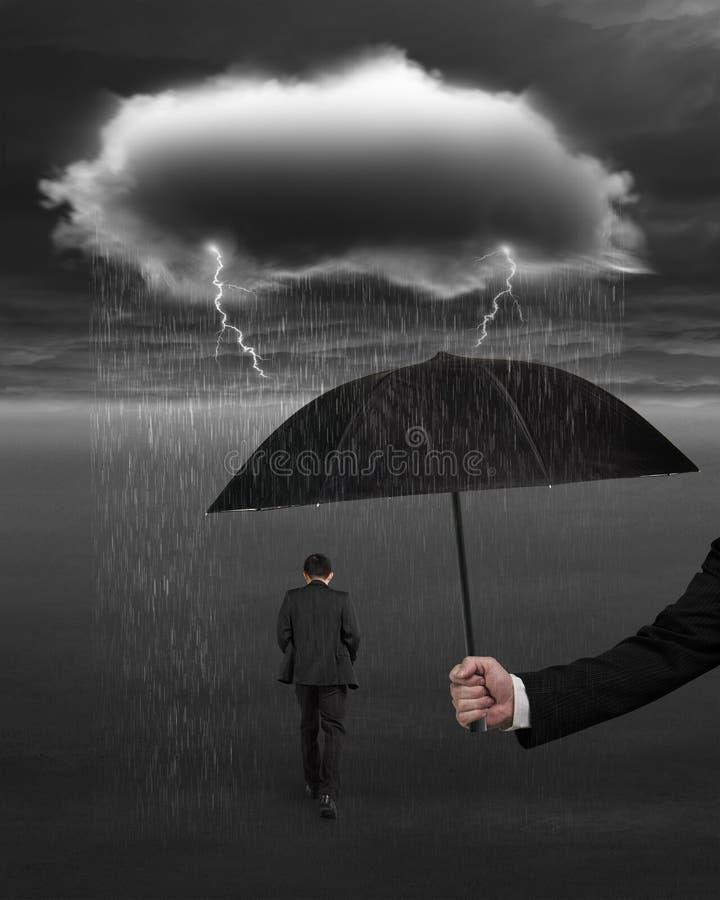 De paraplu die van de handholding zakenman beschermen tegen donkere wolkenrai royalty-vrije stock afbeeldingen