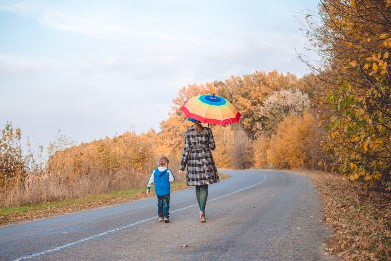 De paraplu die van de vrouwenholding met jongen op de herfst lopen royalty-vrije stock afbeelding