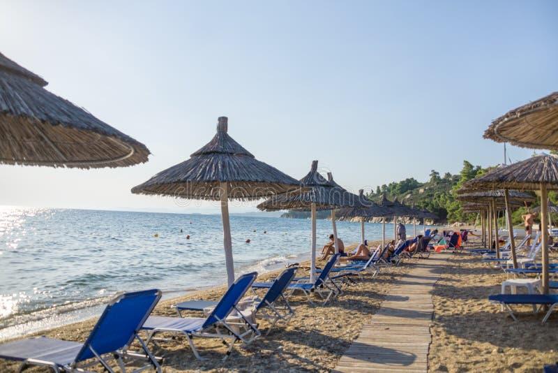 De paraplu's en de ligstoelen schikten in de rij door het overzees op het strand royalty-vrije stock afbeeldingen