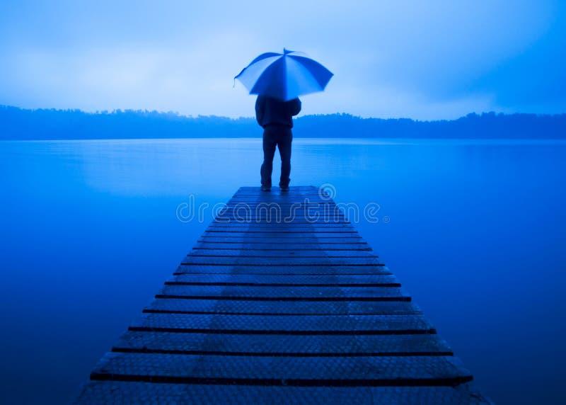 De Paraplu van de mensenholding op een Concept van het Pier Rustig Meer stock fotografie