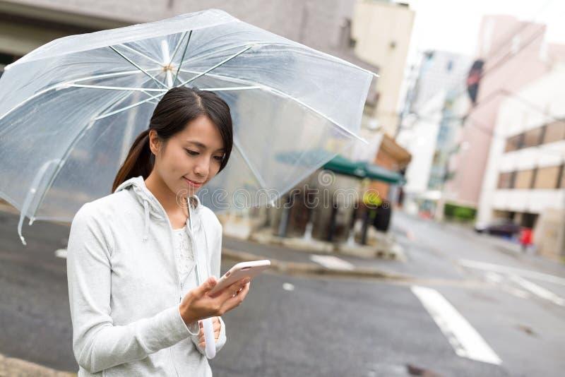 De paraplu van de vrouwenholding en het gebruiken van mobiele telefoon met het regenen outsi royalty-vrije stock fotografie