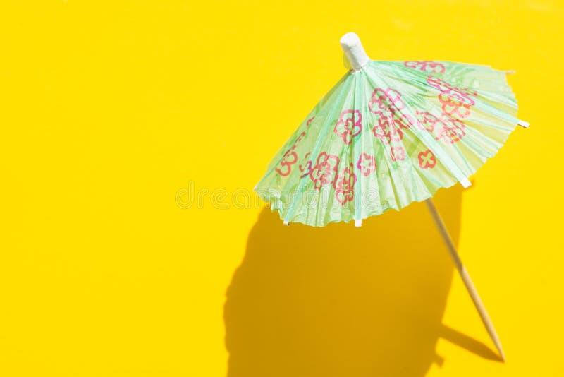 De paraplu van de Groenboekcocktail op heldere gele achtergrond Ruwe lichte harde schaduw In minimalistische pop-artstijl De zome stock foto