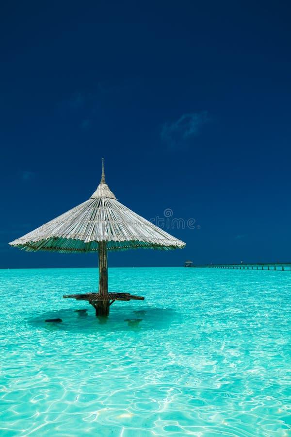De paraplu van het bamboestrand met barzetels in het water van een eiland stock foto
