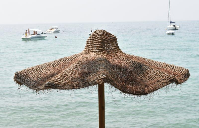 De paraplu van het kokosvezelstrand op de kust van Meer Garda royalty-vrije stock afbeeldingen