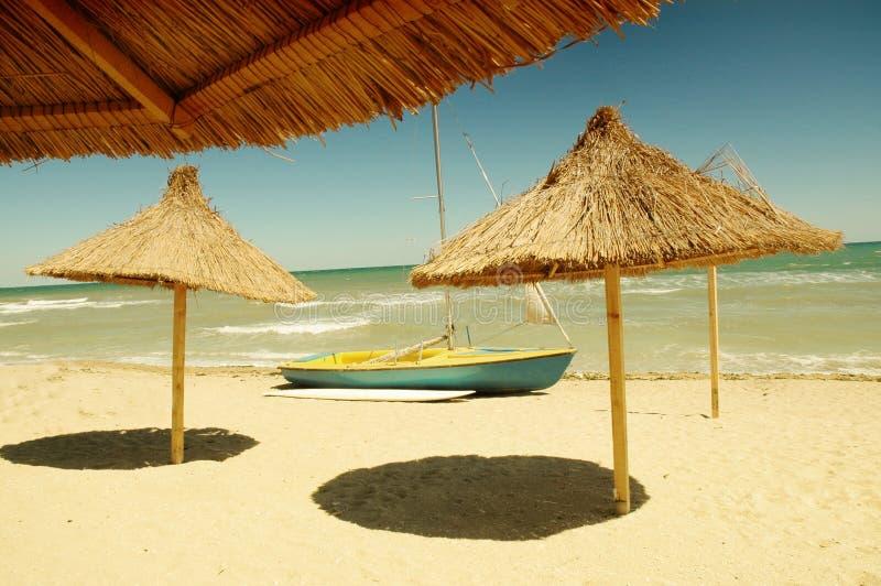 De paraplu van het strand en een boot stock afbeeldingen