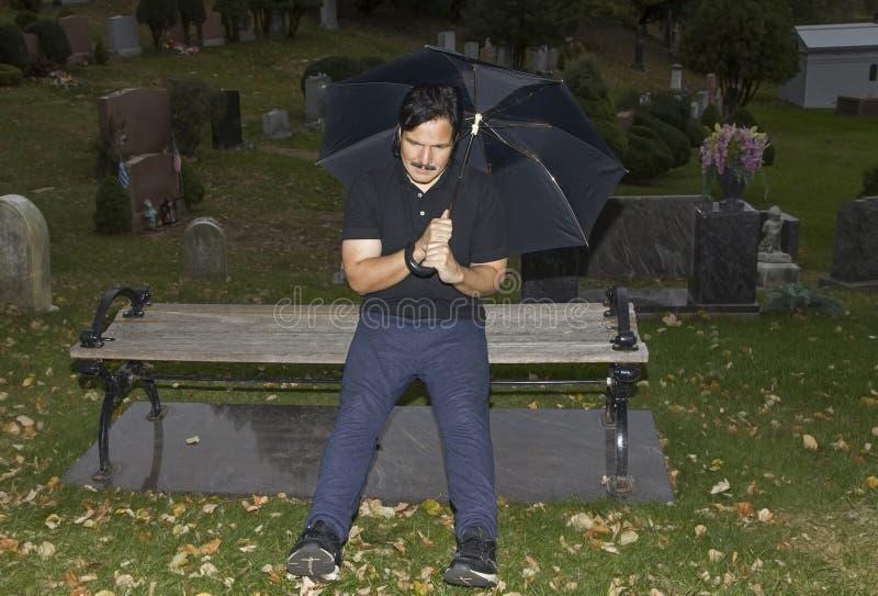 De paraplu van de mensenholding terwijl gezet in een begraafplaats royalty-vrije stock foto