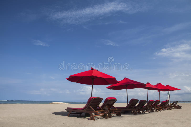 De paraplustoelen van het strand in paradijseiland stock foto's