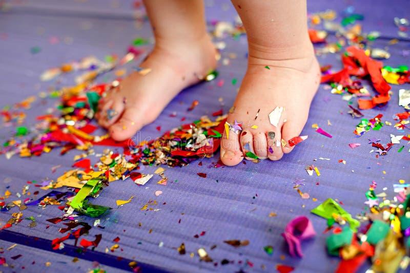 De partij van de kinderen` s verjaardag de naakte voeten zijn op de vloer met confettien stock afbeeldingen