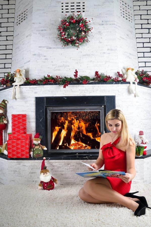 De partij van Kerstmis Jonge mooie blondevrouw die een boek lezen dichtbij een open haard Open haard met Kerstmisdecor royalty-vrije stock foto