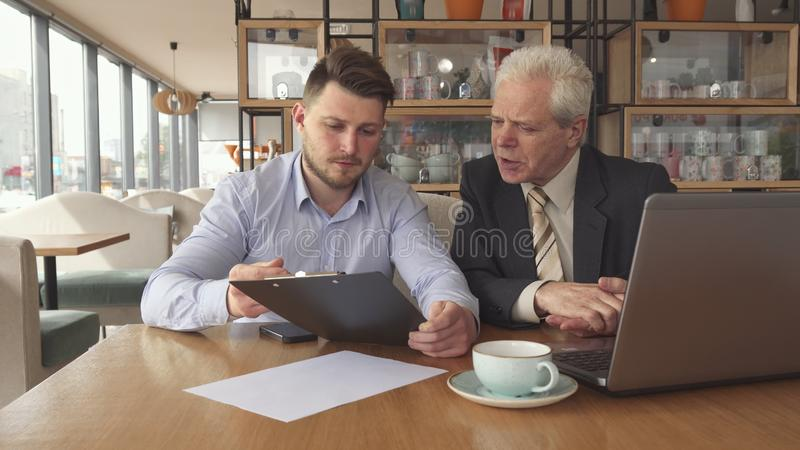 De partners bespreken één of ander project bij de koffie stock foto's