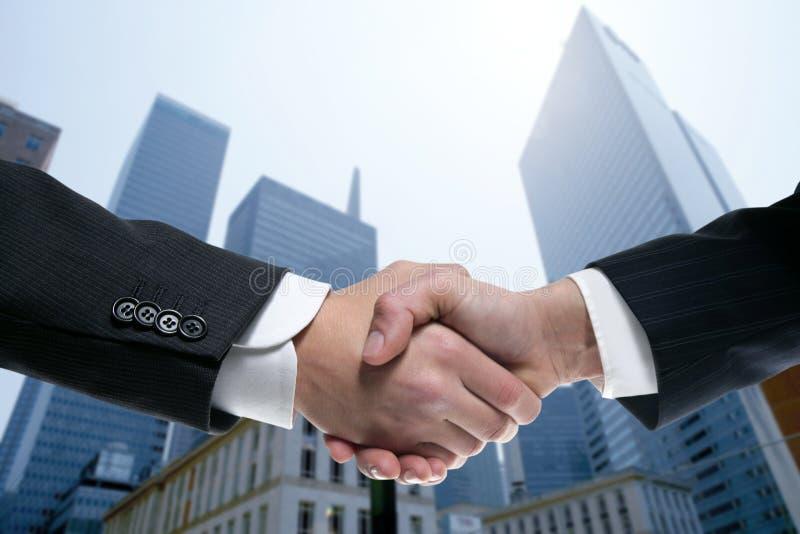 De partners die van de zakenman handen met kostuum schudden stock fotografie