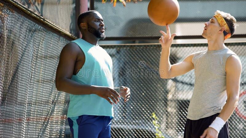 De partners die van het basketbalspel, mensen spinnende bal op vinger, vrienden communiceren royalty-vrije stock foto's