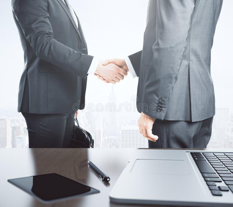 De partners schudden handen en lijst met laptop en agenda royalty-vrije stock foto's