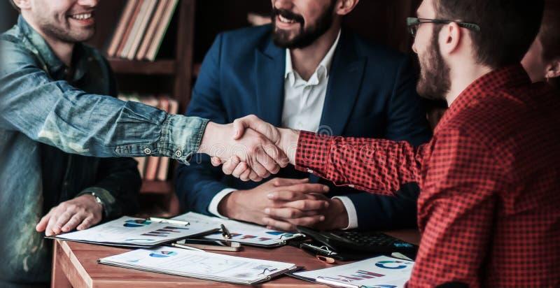 De partners schudden handen na het bespreken van het contract bij t royalty-vrije stock foto